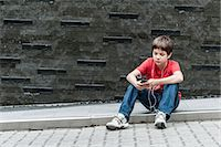 Boy sitting on sidewalk listening to music with earphones Stock Photo - Premium Royalty-Freenull, Code: 632-06029904