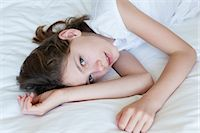 Girl lying on bed, portrait Stock Photo - Premium Royalty-Freenull, Code: 632-06029971