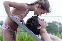 Girl in bikini kissing brother reclining on deckchair Stock Photo - Premium Royalty-Freenull, Code: 632-06030219
