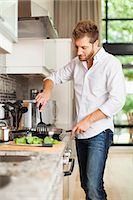 stove - Smiling man cooking in kitchen Stock Photo - Premium Royalty-Freenull, Code: 649-06040115