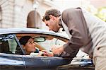 Man talking to woman through car window Stock Photo - Premium Royalty-Free, Artist: Blend Images, Code: 649-06040243