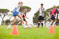 female playing soccer - Coach training childrens soccer team Stock Photo - Premium Royalty-Freenull, Code: 649-06040287