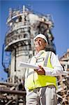 Worker with blueprints at oil refinery Stock Photo - Premium Royalty-Free, Artist: Marc Simon, Code: 649-06040366