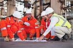 Workers with blueprints at oil refinery Stock Photo - Premium Royalty-Free, Artist: Marc Simon, Code: 649-06040391