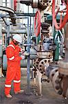 Worker adjusting gauge at oil refinery Stock Photo - Premium Royalty-Free, Artist: Marc Simon, Code: 649-06040402