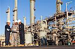 Workers with blueprints at oil refinery Stock Photo - Premium Royalty-Free, Artist: Marc Simon, Code: 649-06040417