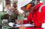 Worker noting gauge at oil refinery Stock Photo - Premium Royalty-Free, Artist: Marc Simon, Code: 649-06040468
