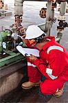 Worker noting gauge at oil refinery Stock Photo - Premium Royalty-Free, Artist: Marc Simon, Code: 649-06040469