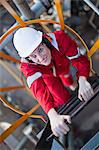 Worker climbing ladder at oil refinery Stock Photo - Premium Royalty-Free, Artist: Marc Simon, Code: 649-06040486