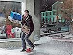 Man dropping Christmas gifts in snow Stock Photo - Premium Royalty-Free, Artist: Science Faction, Code: 649-06041426