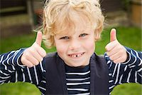 Smiling boy giving thumbs-up outdoors Stock Photo - Premium Royalty-Freenull, Code: 649-06041770