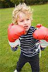 Boy playing with boxing gloves outdoors Stock Photo - Premium Royalty-Freenull, Code: 649-06041781