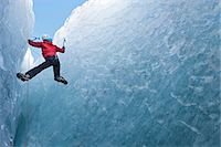 Climber climbing out of ice cave Stock Photo - Premium Royalty-Freenull, Code: 649-06041884
