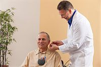Audiologist inserting behind-the-ear hearing aid into a patient's ear during programming Stock Photo - Premium Royalty-Freenull, Code: 6105-06042975