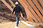 Carpenter with a nail gun at roof level Stock Photo - Premium Royalty-Free, Artist: Norbert Schäfer, Code: 6105-06043017