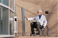 Doctor with muscular dystrophy in wheelchair at hospital entrance pressing knob for accessible door Stock Photo - Premium Royalty-Freenull, Code: 6105-06043127