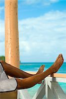 paradise (place of bliss) - Man on vacation with legs resting on veranda rail Stock Photo - Premium Royalty-Freenull, Code: 614-06043822