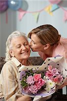 Daughter giving senior mother bouquet of flowers Stock Photo - Premium Royalty-Freenull, Code: 614-06043881