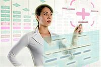 Woman interacting with holographic screens Stock Photo - Premium Royalty-Freenull, Code: 614-06043999
