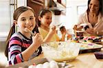 Portrait of girl making cakes with family in kitchen Stock Photo - Premium Royalty-Free, Artist: Cultura RM, Code: 614-06044387
