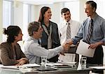 Businessman shaking hands in office with colleagues Stock Photo - Premium Royalty-Free, Artist: Blend Images, Code: 614-06044411