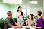 Office colleagues discussing new technologies on desk Stock Photo - Premium Royalty-Free, Artist: Ikon Images, Code: 614-06044507