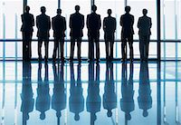 Silhouette of business people in a row looking out lobby window Stock Photo - Premium Royalty-Freenull, Code: 635-06045044