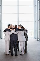 Business people standing in huddle Stock Photo - Premium Royalty-Freenull, Code: 635-06045094
