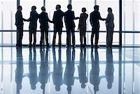 Business people shaking hands in a row at lobby window Stock Photo - Premium Royalty-Freenull, Code: 635-06045104