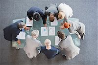 Business people huddled around paperwork on table Stock Photo - Premium Royalty-Freenull, Code: 635-06045106