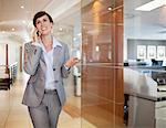 Smiling businesswoman talking on cell phone in office corridor