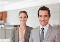 Portrait of smiling businessman and businesswoman in office Stock Photo - Premium Royalty-Freenull, Code: 635-06045159
