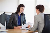 Businesswomen with paperwork talking face to face Stock Photo - Premium Royalty-Freenull, Code: 635-06045215