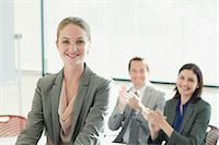 Co-workers clapping for smiling businesswoman Stock Photo - Premium Royalty-Freenull, Code: 635-06045227