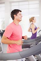 Smiling man running on treadmill in gymnasium Stock Photo - Premium Royalty-Freenull, Code: 635-06045263