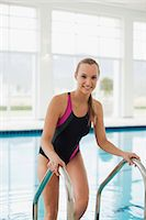 Smiling woman in bathing suit stepping out of swimming pool Stock Photo - Premium Royalty-Freenull, Code: 635-06045331