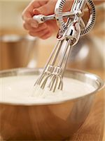 Woman whisking cream with egg beater Stock Photo - Premium Royalty-Freenull, Code: 635-06045522