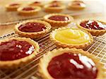 Close up of jam tarts cooling on wire racks Stock Photo - Premium Royalty-Free, Artist: Blend Images, Code: 635-06045547