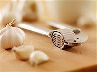 Close up of garlic and garlic press on cutting board Stock Photo - Premium Royalty-Freenull, Code: 635-06045554