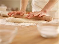 Woman pressing dough with rolling pin Stock Photo - Premium Royalty-Freenull, Code: 635-06045565