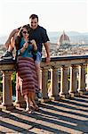 Italy, Florence, Couple viewing camera at lookout over old town Stock Photo - Premium Royalty-Free, Artist: Blend Images, Code: 640-06049924