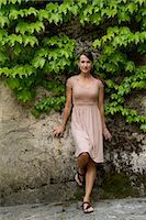Italy, Ravello, Portrait of woman in dress leaning overgrown wall Stock Photo - Premium Royalty-Freenull, Code: 640-06050023