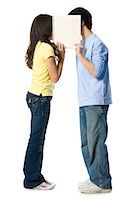 preteen kissing - young couple holding a sign Stock Photo - Premium Royalty-Freenull, Code: 640-06051407