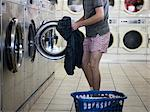 man taking off clothes at a laundromat Stock Photo - Premium Royalty-Free, Artist: CulturaRM, Code: 640-06051903