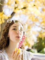 Young woman blowing soap bubbles in Autumn forest Stock Photo - Premium Royalty-Freenull, Code: 640-06052211