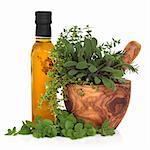 Olive oil bottle with fresh herb leaves in a wooden mortar with pestle over white background. Stock Photo - Royalty-Free, Artist: marilyna                      , Code: 400-06061959