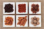 Saffron, star anise, cloves, cinnamon sticks, nutmeg and mace spice in white porcelain dishes over hessian background. Stock Photo - Royalty-Free, Artist: marilyna                      , Code: 400-06062669