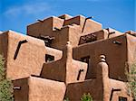 The facade of a hotel built to look like an old native American pueblo with adobe walls, square corners, exposed beams, and more. Stock Photo - Royalty-Free, Artist: searagen                      , Code: 400-06065223
