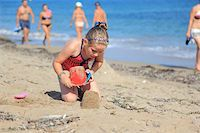 Kids playing with plastic toys on the beach Stock Photo - Royalty-Freenull, Code: 400-06074791