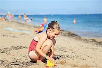 Kids playing with plastic toys on the beach Stock Photo - Royalty-Freenull, Code: 400-06074792